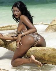 Nice exotic beautiful ebony lies on the beach showing tits